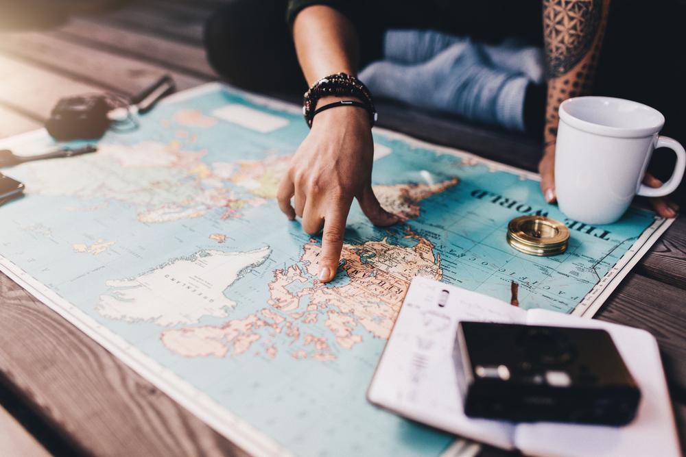Mulher apontando no mapa o seu próximo destino de viagem (imagem ilustrativa). Texto: franquia perfeita.