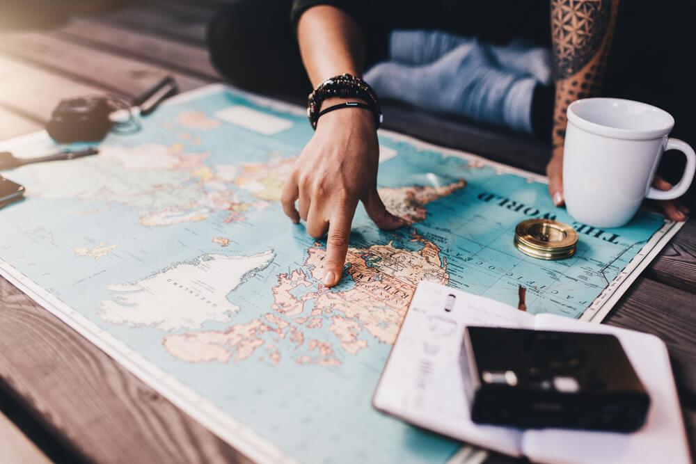 Renda extra: uma pessoa apontando no mapa um lugar que deseja viajar junto com máquina e um xicara