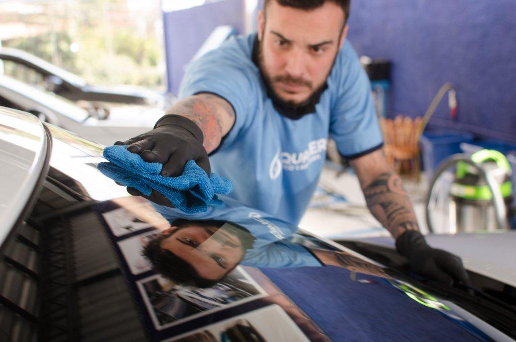 Funcionário da Acquazero, devidamente protegido por luvas, realiza a limpeza do para-brisa de um carro (imagem ilustrativa). Texto: opções de franquias baratas.