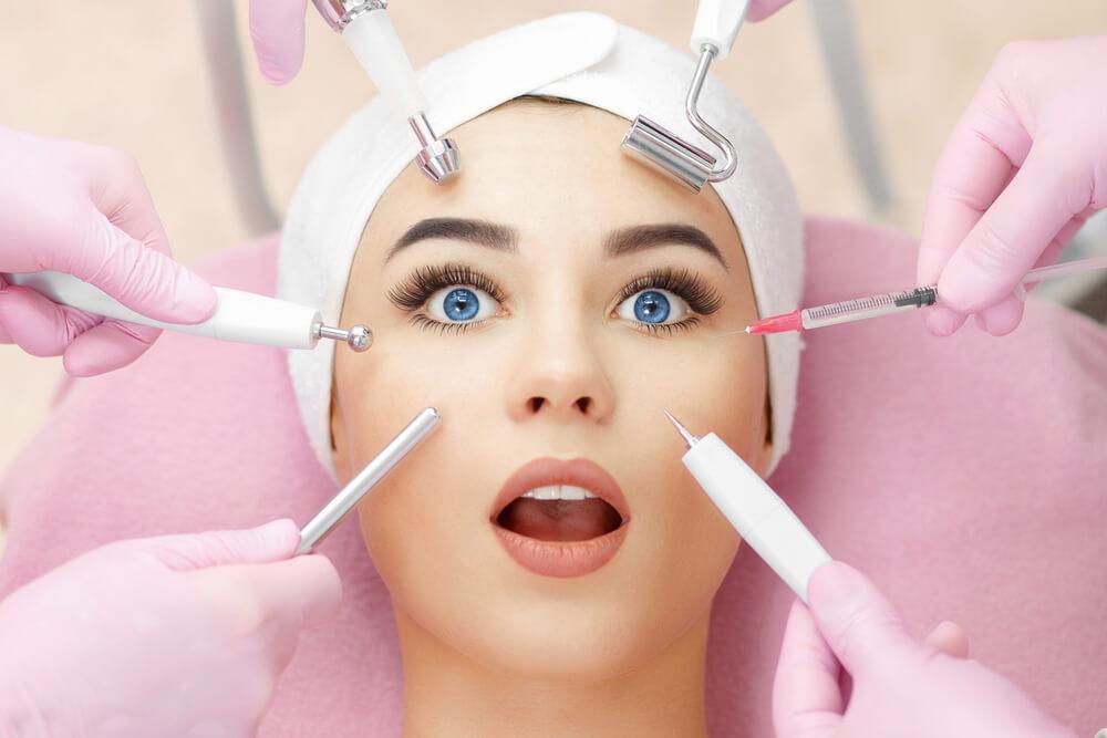 franquias de beleza: Mulher deitada com diversos aparelhos para estética apontados para seu rosto