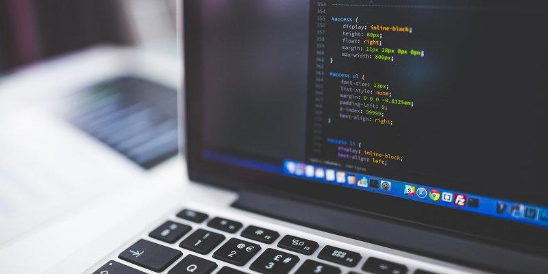 Foto de parte de uma tela de um computador cinza, com alguns códigos aparecendo, temos uma mesa branca em um fundo desfocado. Imagem ilustrativa para texto franquia digital Contele.