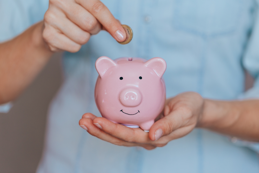 Homem depositando moeda no cofre em formato de porco (imagem ilustrativa). Texto: modelos de franquias para trabalhar home office.