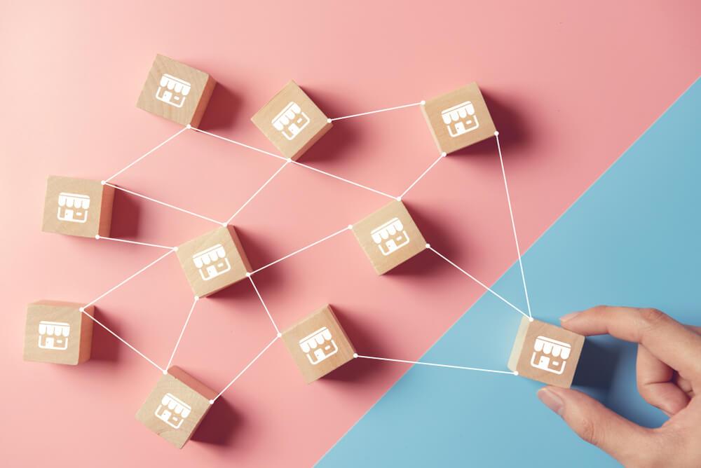 """vários blocos de madeira cuja representação imagética de uma lógica está desenhadas. Os """"blocos-loja""""estão interligados em uma rede imagem ilustrativa texto empresas lucrativas"""
