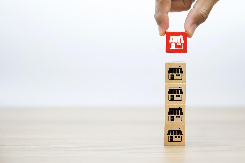 Negócios em alta: Blocos de madeira montando uma rede de franquia. Cada um com uma lojinha desenhada