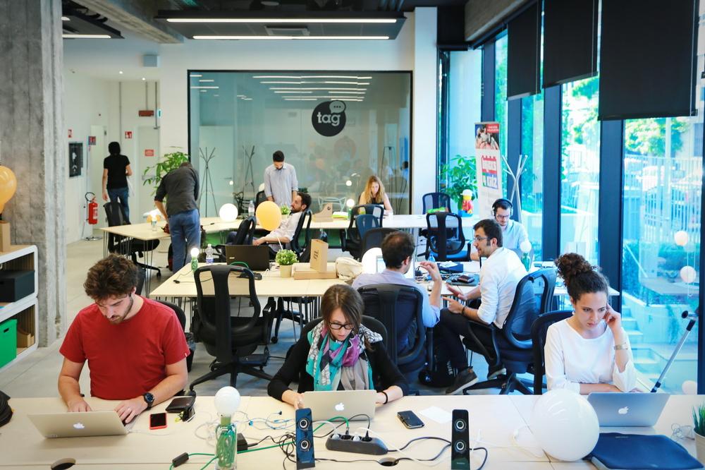 várias pessoas trabalhando em uma sala com várias mesas e cadeiras