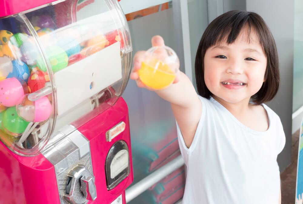criança feliz segurando uma bolinha ao lado de uma máquina