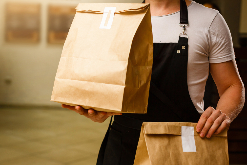 franquias baratas: homem fazendo entrega com duas embalagens lacradas na mão