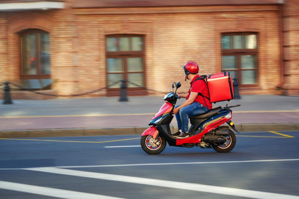 """Vemos um homem em uma motocicleta. Trajando capacete e as famosas """"mochilas de entrega"""", ele segue por uma rua (imagem ilustrativa). Texto: franquia rap chef."""