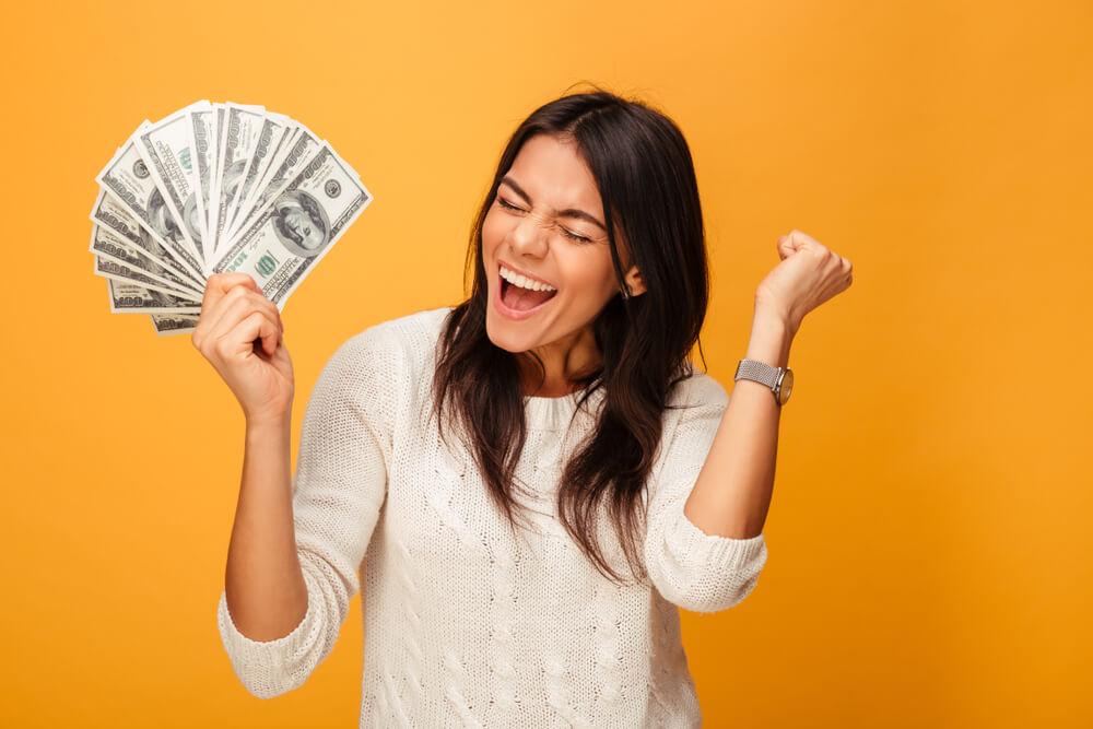mulher feliz e comemorando com um leque de dólares