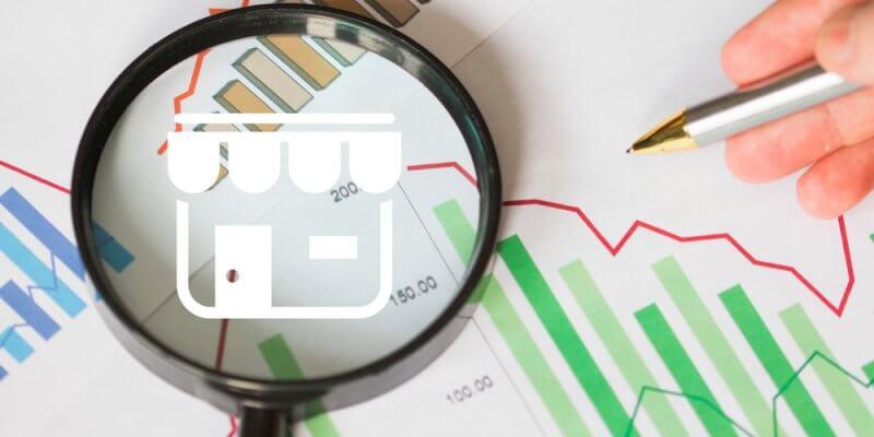 Imagem de uma lupa sobre gráficos. Dentro da lupa está desenhado uma loja imagem ilustrativa texto empresas lucrativas