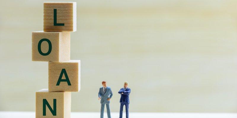 """Blocos escrevendo """"Loan"""", empréstimo em inglês, mais dois bonequinhos simulando empresários. Imagem ilustrativa texto empréstimo para abrir uma franquia."""