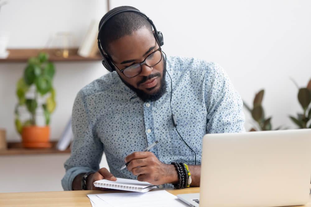 Homem negro e bem-vestido, em frente ao computador, com fones de ouvido, caneta e caderno na mão, estuda (imagem ilustrativa). Franquia de lava jato
