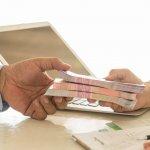 Homem entregando maço de dinheiro para outra pessoa. magem ilustrativa texto financiamento para abrir uma franquia: