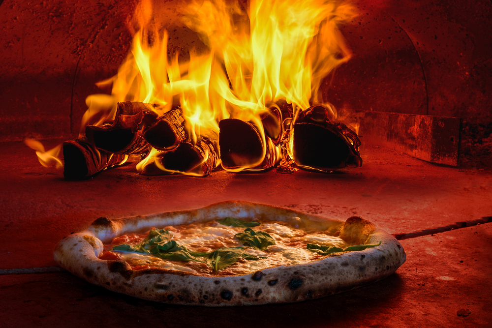 Uma pizza é assada em um forno de pedra (imagem ilustrativa). Texto: opções de franquias baratas