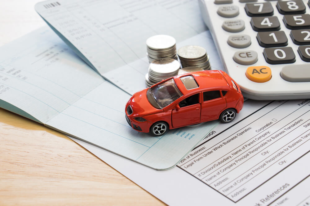 Trabalhar em casa: Carrinho ao lado de moedas e uma calculadora, sobre algumas contas