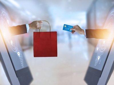 Franquia de loja virtual: Duas mãos saindo de dois monitores em frente um do outro. Uma mão entregando o cartão e a outra com sacola de compras