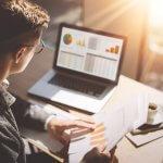 Franquia de marketing: Homem a analisando dados em seu notebook e comparando com relatório impresso no escritório da empresa