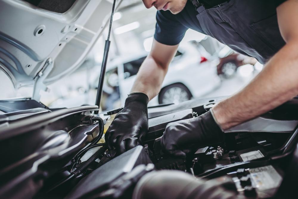 Mecânico analisa parte interna de um veículo.