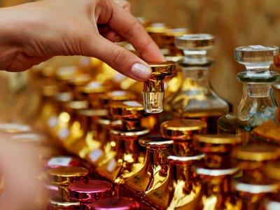 Mulher pegando tampa de um frasco de perfume. Estande com vários frascos diferentes. Imagem ilustrativa texto franquia de perfurmaria.