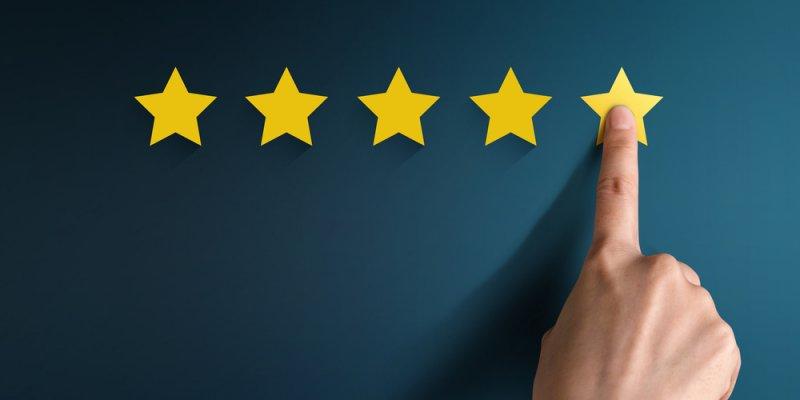 Homem apontando para 5 estrelas presas na parede. Imagem ilustrativa texto franquia perfeita