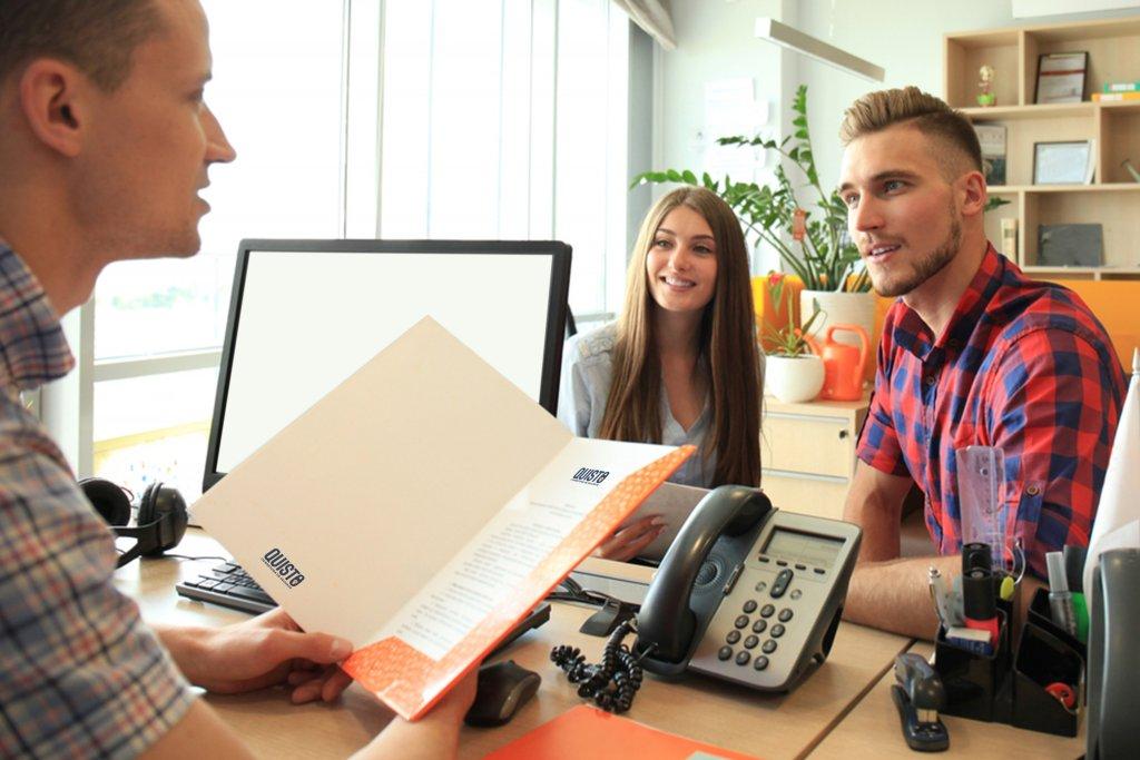 Homem com proposta da Quisto em mãos para oferecer ao casal de clientes ao fundo (imagem ilustrativa). Texto: franquias home based.