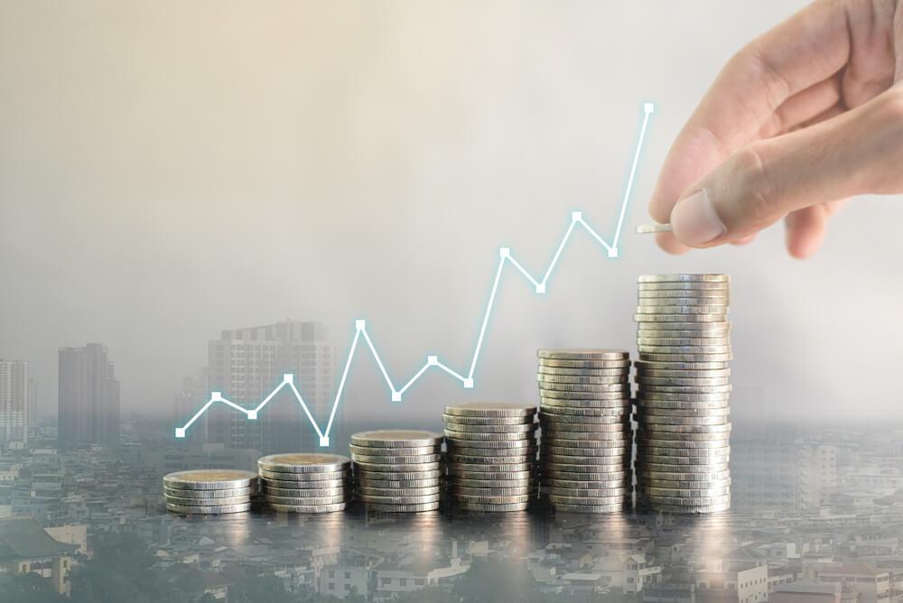 renda extra: Imagem de moedas formando uma escadinha e com gráfico apontando crescimento