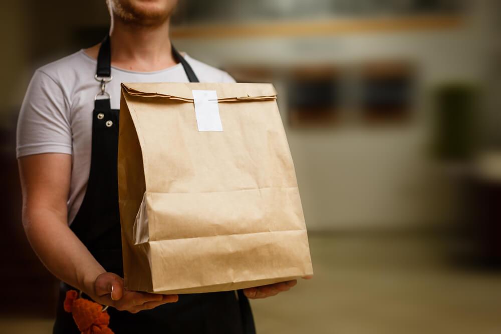 Trabalhar em casa: Homem fazendo a entrega de uma mercadoria embalada