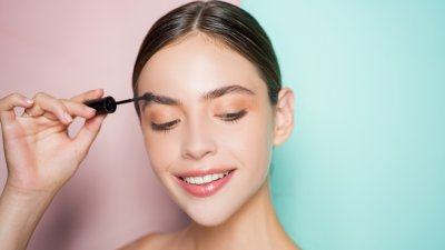Franquia de beleza: mulher passando rímel e sorrindo