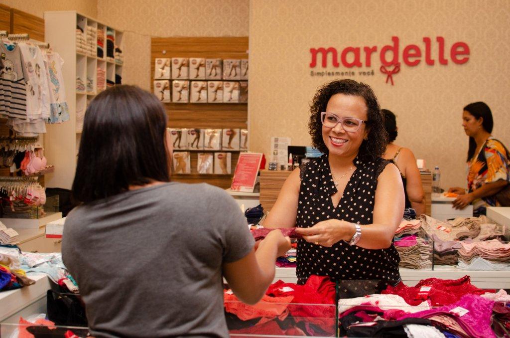 Fundadora da Mardelle entrega peça a cliente em sua loja (imagem ilustrativa). Texto: opções de franquias baratas.