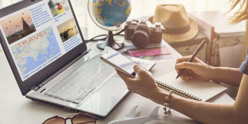 Franquias de tecnologia: Mulher comparando informações do computador com seu celular e anotando em uma caderneta.