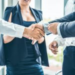 Homens e mulher de negócios apertando as mãos selando um acordo. Imagem ilustrativa texto fusão de franquias.