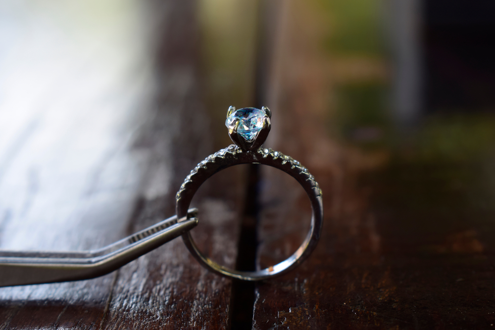 Seguro por uma pinça há um anel com brilhante parecendo um diamante (imagem ilustrativa). Texto: microfranquias baratas.