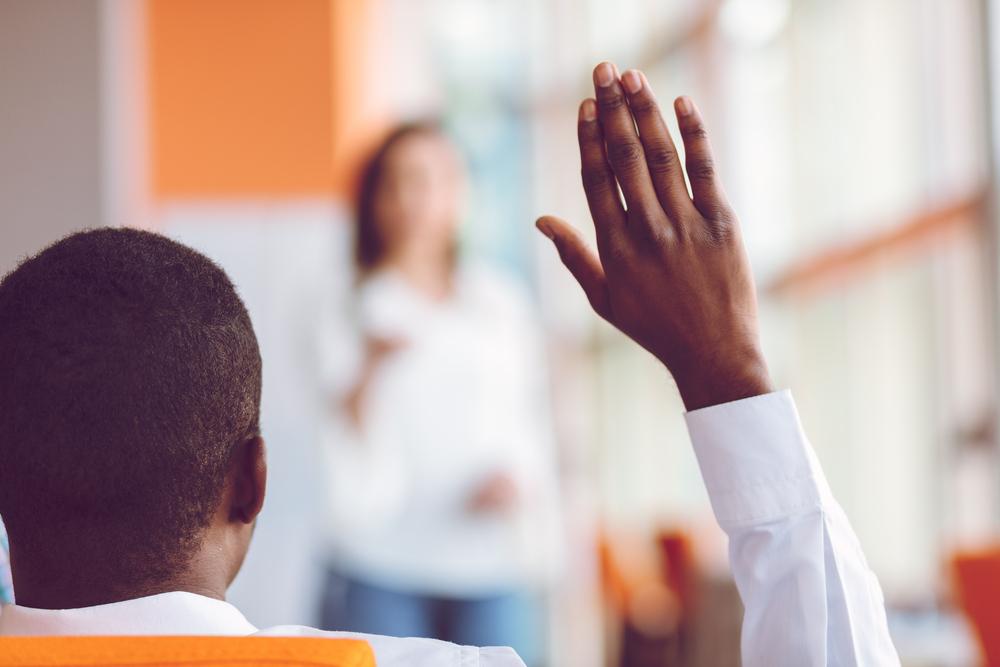 Homem levantando a mão durante uma aula