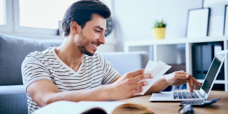 Homem analisando informação de um papel e checando no computador. Imagem ilustrativa texto negócio próprio