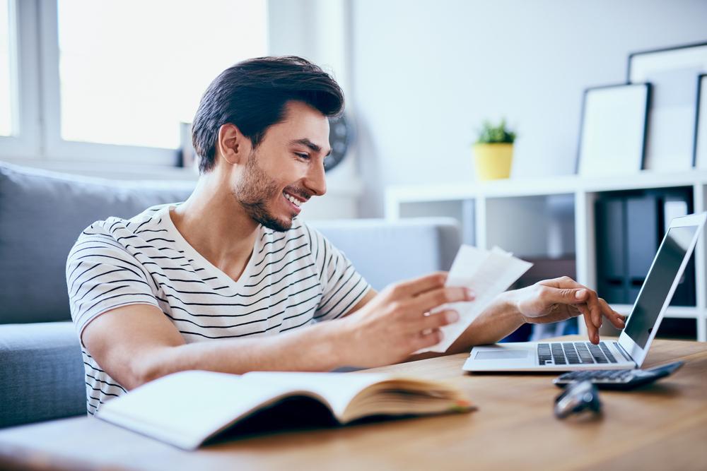 Um homem está na sala de casa. Ele segura alguns papéis na mão direita enquanto digita em seu computador com a esquerda. À mesa temos um caderno aberto, seus óculos e uma calculadora (imagem ilustrativa). Texto: franquia home office.