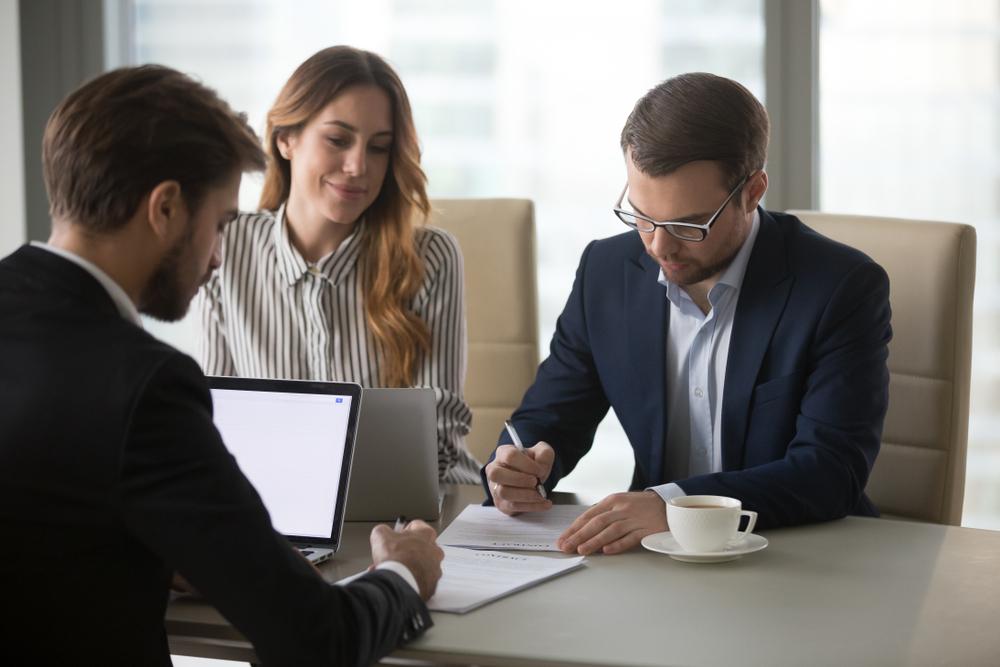 Dois homens de vestimenta social lêem um documento enquanto uma mulher, também de vestimenta social, realiza uma pesquisa eu seu computador. Imagem ilustrativa. Texto: franquias confiáveis.