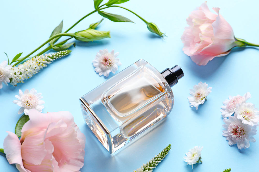 Frasco de perfume em um fundo azul com flores aromáticas ao lado. Imagem ilustrativa. Texto: franquia de perfumaria