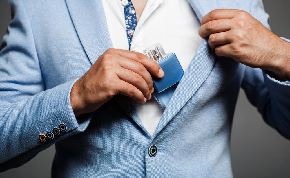 Homem muito bem vestido retira frasco de perfume do bolso de seu paletó. Imagem ilustrativa. Texto franquia de perfumaria.