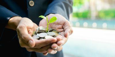 Renda extra: homem segurando várias moedas com uma plantinha, dando a entender que está plantando algo