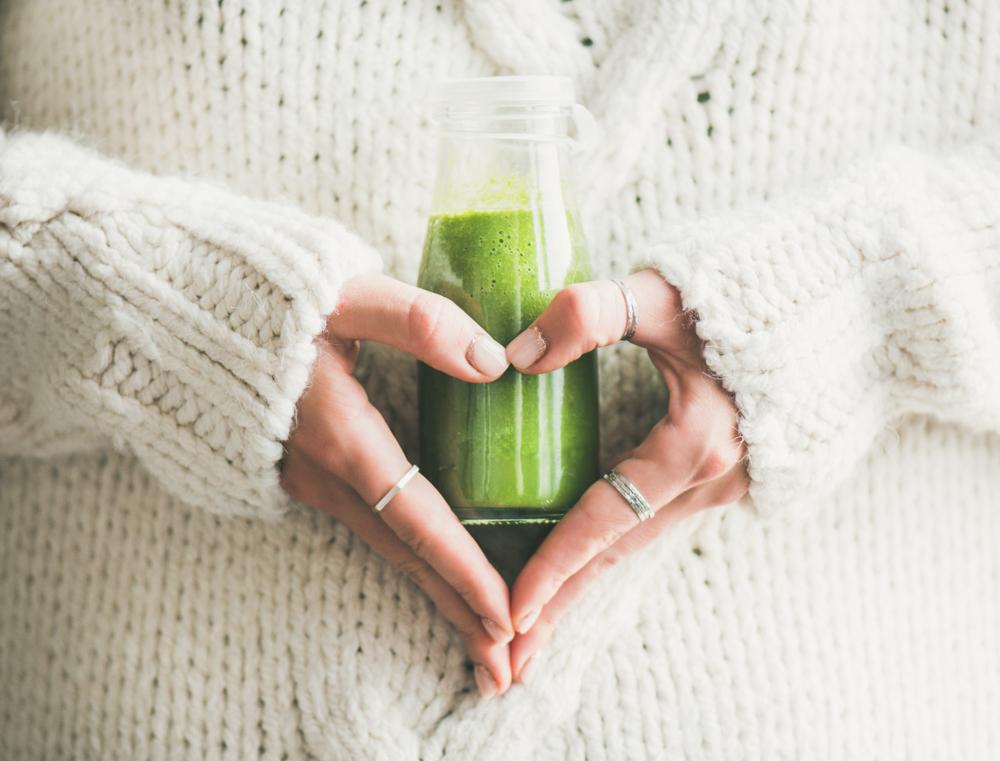 Mulher segura uma garrafa com suco verde formando coração com a mão.