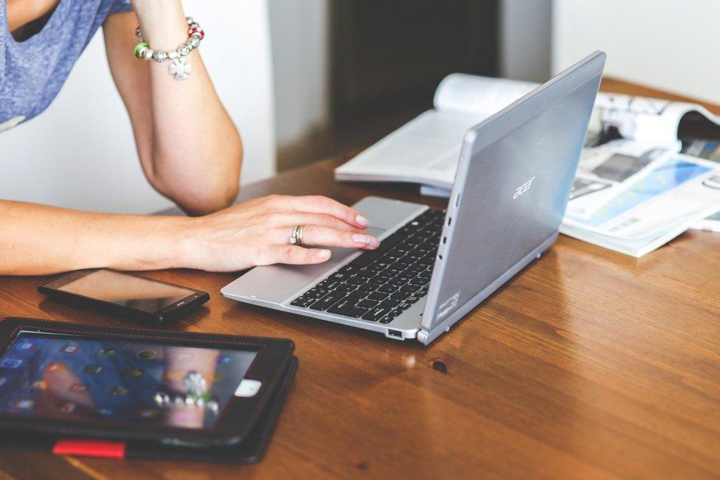 Vemos uma mão feminina mexendo no notebook em sua casa (imagem ilustrativa). Texto: franquia Mazze.