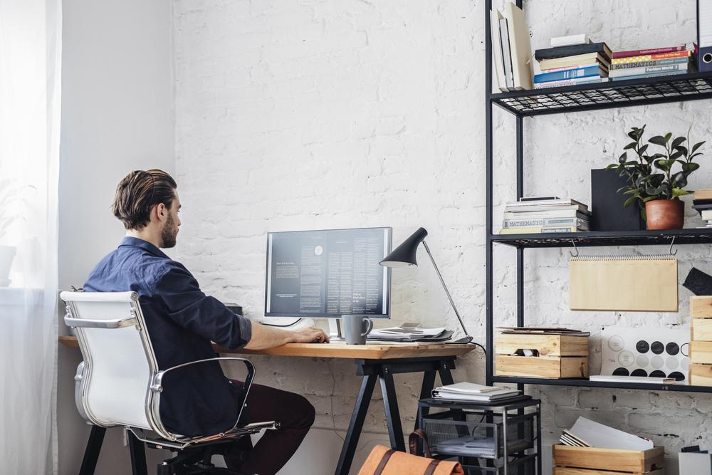 Homem, em seu escritório, toma café enquanto organiza uma grande quantidade de informação na tela de seu computador (imagem ilustrativa). Franquia de loja virtual