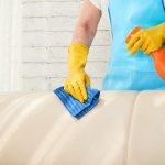 Foto de uma pessoa com avental azul e luva amarela segurando uma flanela azul e borrifador laranja para limpar sofá bege. Ao fundo temos uma parede branca. Imagem ilustrativa para texto franquia Doutor Sofá expansão