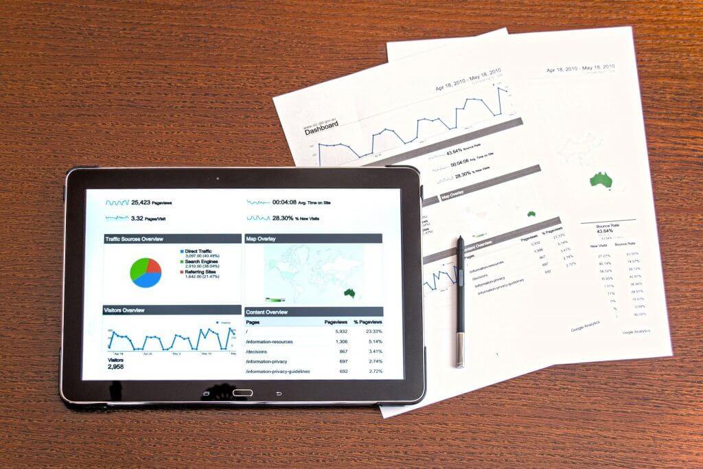 Foto de um tablet preto, alguns gráficos em tela; ao lado de alguns papeis também com vários dados e informações.