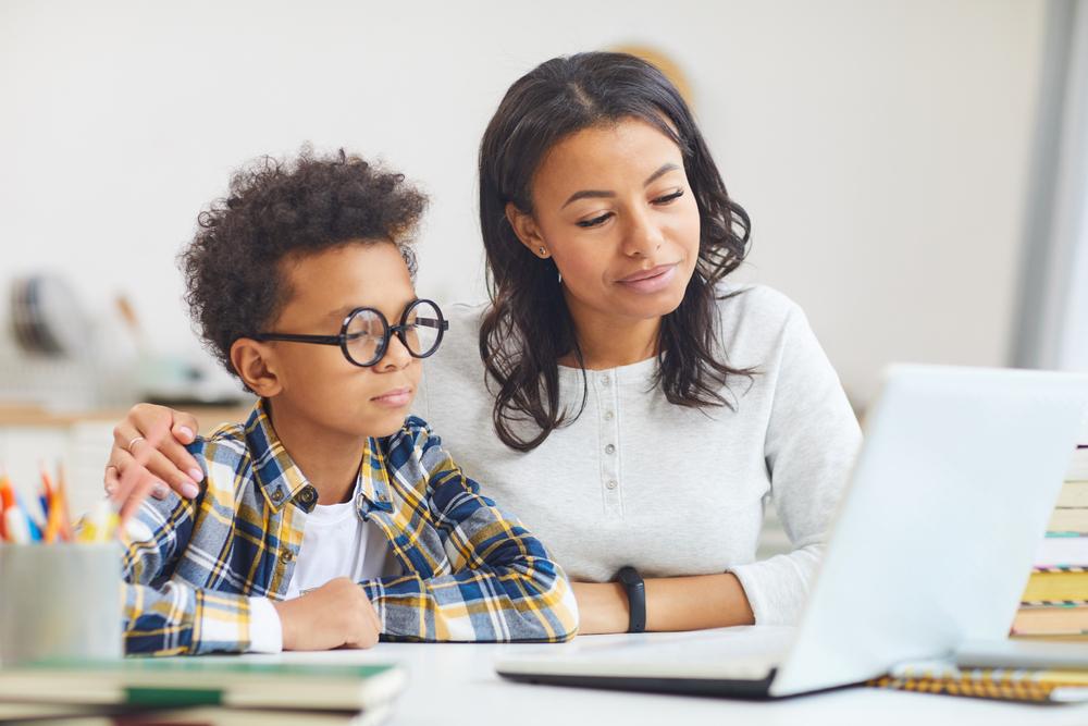 Uma mulher está ao lado do seu filho. Ambos olham para a tela do computador.
