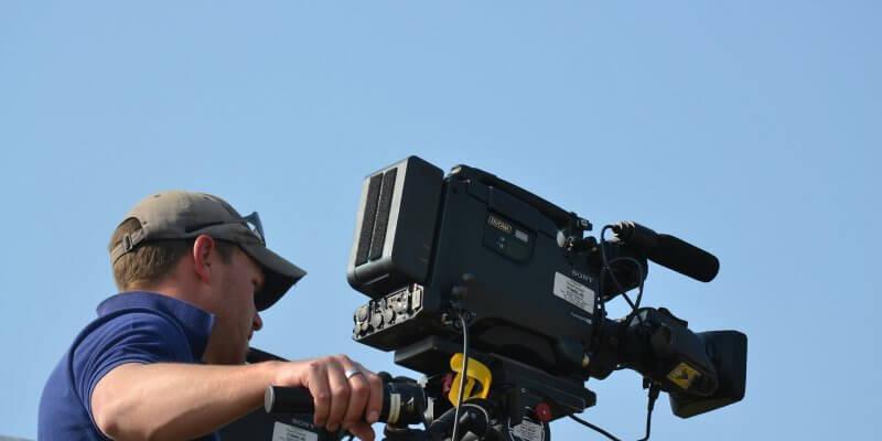 Foto de um cinegrafista com blusa azul segurando uma câmera de filmagens. Ao fundo temos o céu azul. Imagem ilustrativa para texto franquia Artes Filmes.