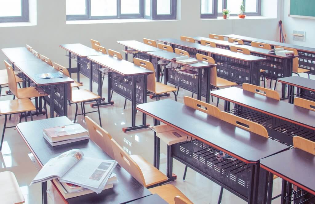 Foto de uma sala de aula toda branca com janelas ao fundo. Temos carteiras e cadeiras pretas com detalhes em madeira alinhados em duas fileiras (imagem ilustrativa). Texto: enjoy expansão.