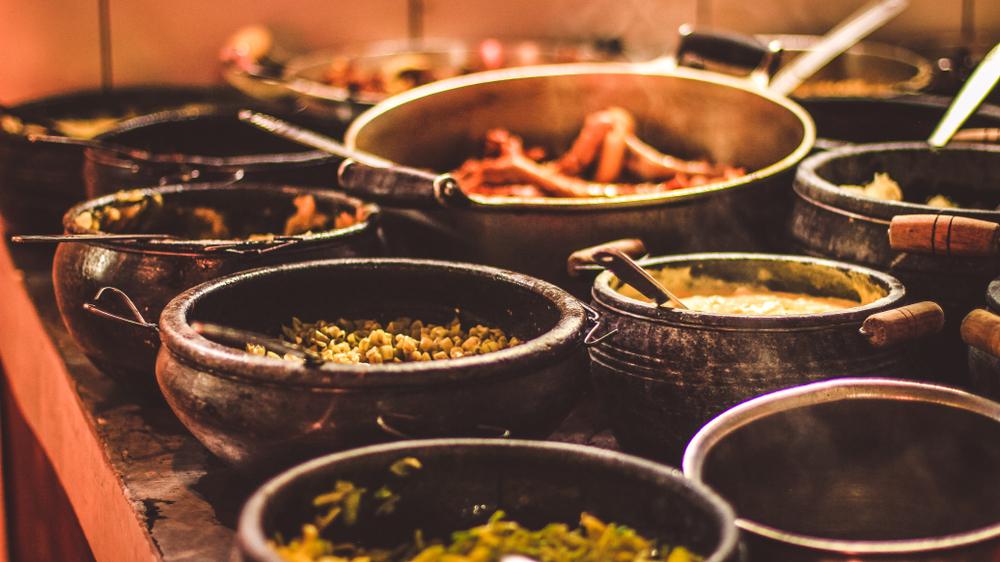 Várias panelas de pedra e barro sobre um fogão de lenha com comidas típicas de minas.