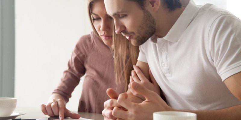 Casal olhando um documento importante. Imagem ilustrativa texto como ganhar dinheiro com franquia