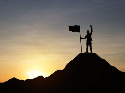 Empresário no topo de uma montanha com bandeira fincada. Imagem ilustrativa texto empreendedores de sucesso